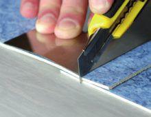 Разрежьте полосы напольного покрытия, уложенные внахлест (3–5 см), с помощью ножа и металлической линейки/планки (метод резки внахлест)