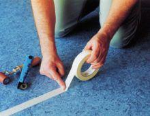 Очистите зону шва от грязи и приклейте бумажный скотч на се- редину плотно резаного шва