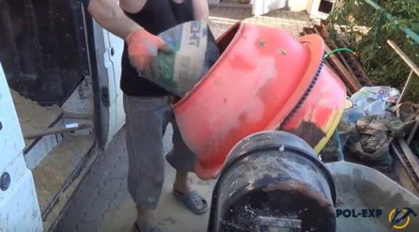 Засыпка цемента в бетономешалку. Для удобства он добавляется туда из обрезанной половины бумажного мешка – это значительно ускоряет процесс