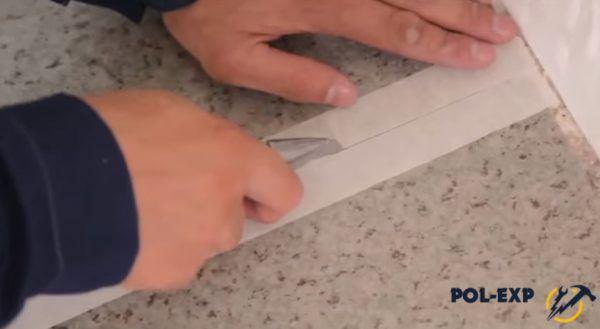 Мастер прорезает скотч по всей длине