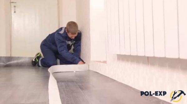 Мастер срезает излишки материала по всему периметру комнаты