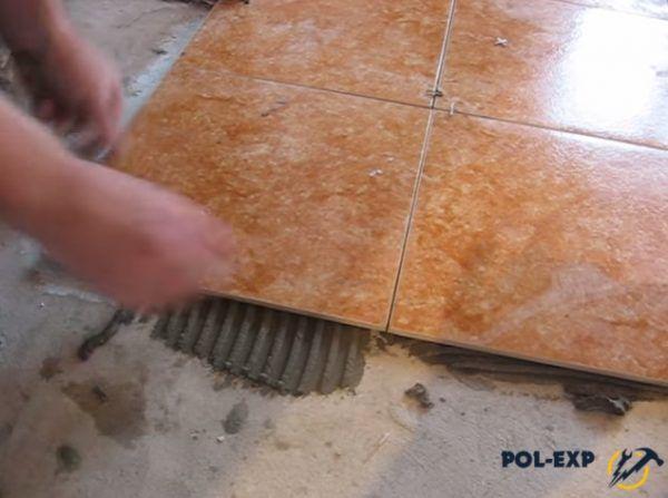 Прижмите плитку к полу