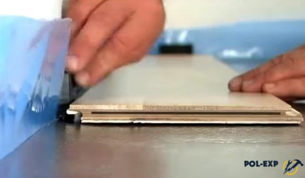 На фото показан процесс укладки паркетной доски и установки клиньев