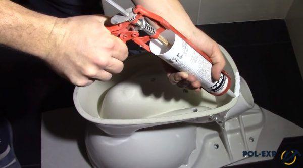 Переверните унитаз, нанесите слой клея или сантехнического герметика