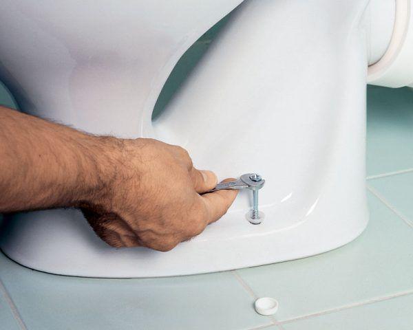 Винт нужно вкручивать аккуратно во избежание появления трещины на унитазе