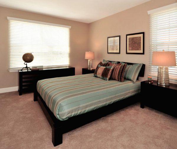 Розовый пол под мрамор и розовые стены удачно сочетаются с чёрной кроватью, чёрными прикроватными тумбочками