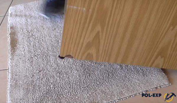 Коврик заправляется под приподнятый край мебели