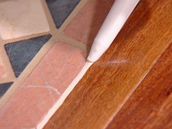 Стык между плиткой и ламинатом заполняется герметиком