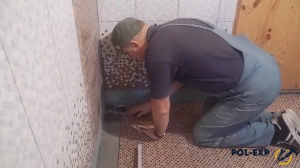 Процесс укладки плитки около трапа
