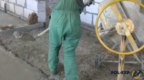 Мастер укладывает бетон совковой лопатой