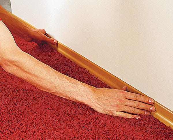 Можно закрепить ковролин обычным плинтусом, приклеенным на монтажный клей