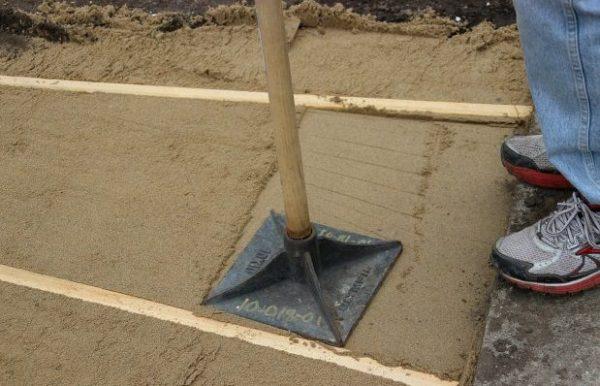 Ручная трамбовка. Владельцы частных домов также могут изготовить подобный инструмент самостоятельно из одного достаточно толстого бревна длиной 1 м и нескольких досок