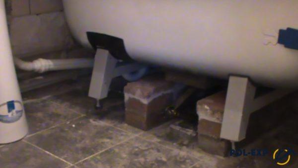 Под ванной установлен домкрат, уложены кирпичи