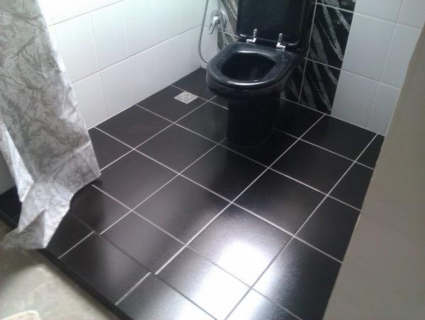 В некоторых случаях допускается отойти от предпочтения светлой плитки для пола и обратить внимание на материалы темных цветов, если они будут визуально расширять помещение за счет контраста с отделкой стен
