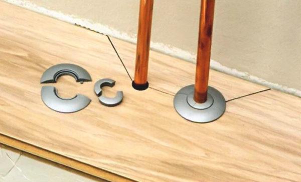 При укладке ламината используются пластиковые розетки для труб отопления