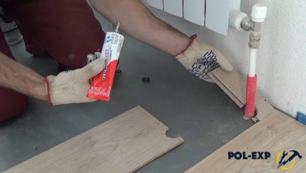 Укладка подготовленного куска (мастер промазывает стыки герметиком, т. к. ламинат укладывается на кухне)