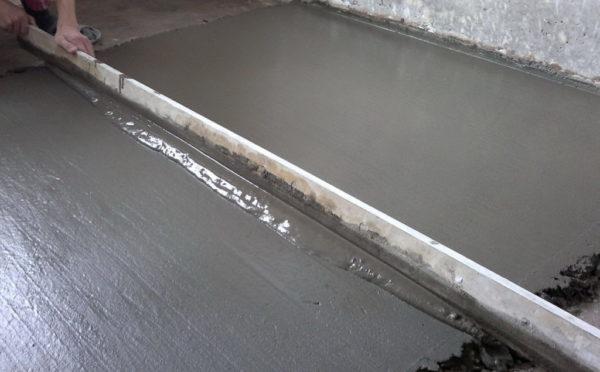 Выравнивание бетонного пола при помощи правила