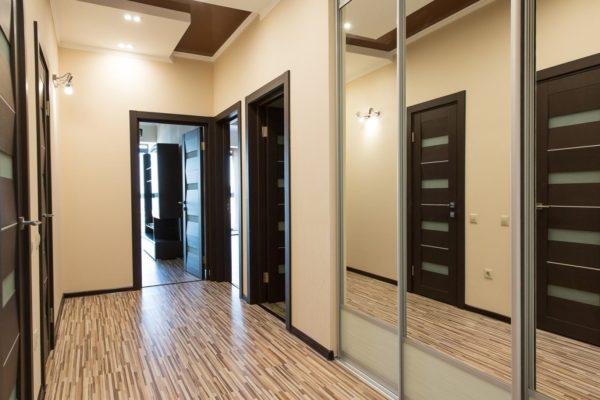 Если коридор короткий и узкий, то зрительно удлинить его поможет выраженный продольный рисунок на поверхности напольного покрытия