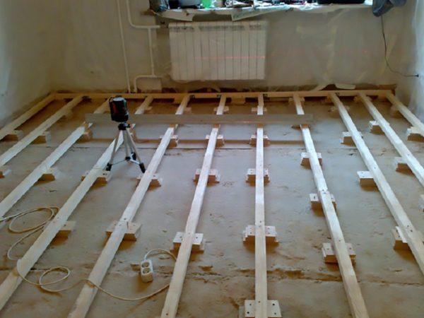 Маяковые лаги для деревянного пола — для регулировки их высоты используют деревянные бруски, фанеру или др. материалы. Горизонтальность лаг тоже проверяют, используя уровень