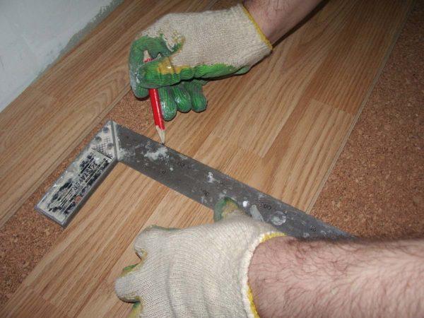 Перед тем как пилить ламинат, на его поверхности отмечают линию реза