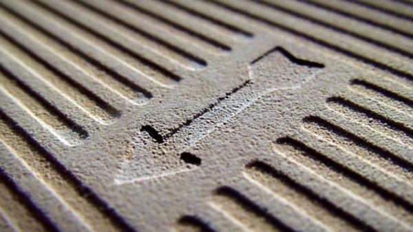 Оборотная сторона плитки имеет условные обозначения и углубления для улучшения адгезии с клеем