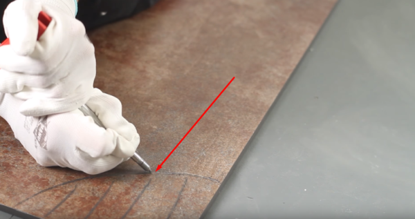 С помощью специального инструмента обводят (царапают) линию отреза