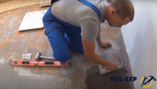 Плиточный клей растирается по полу
