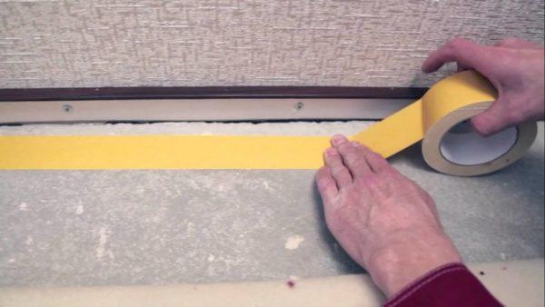 Скотч фиксируют по периметру помещения и в центре с шагом примерно 60 см