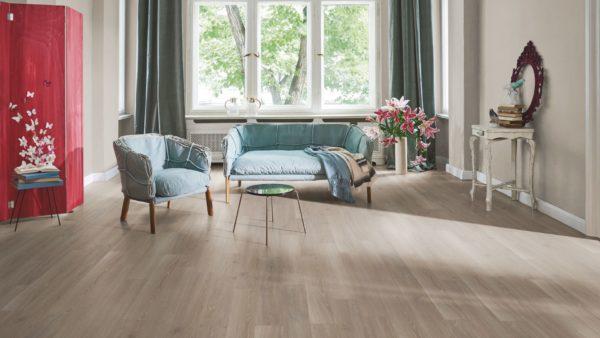 Ламинат теплого оттенка поддержан однотонными стенами того же цвета – на их фоне естественно смотрится холодный серо-голубой текстиль и обивка мебели
