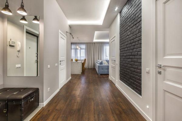 Коридор в классическом стиле с серыми стенами и темным полом