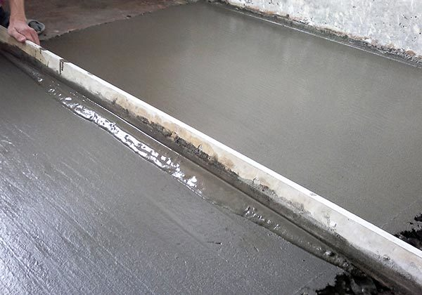 Равнение правилом бетонной стяжки