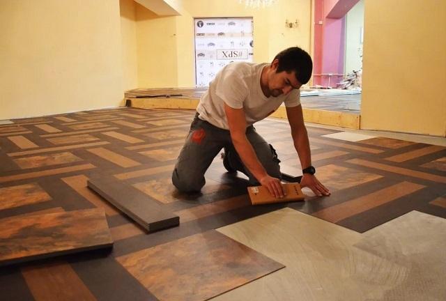 Мастер за работой – укладка напольного покрытия из плитки разного размера, форм и расцветок
