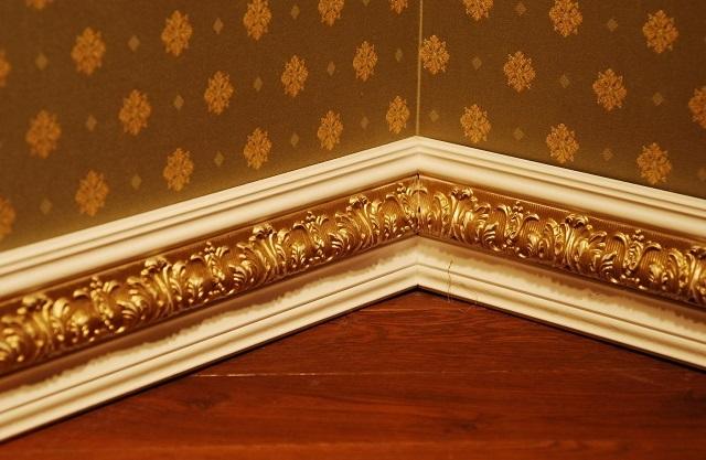Полиуретановый плинтус с золоченым рельефным рисунком – после монтажа и декорирования.