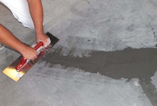 Нанесение нового раствора на повреждения старой стяжки, требующей ремонта.